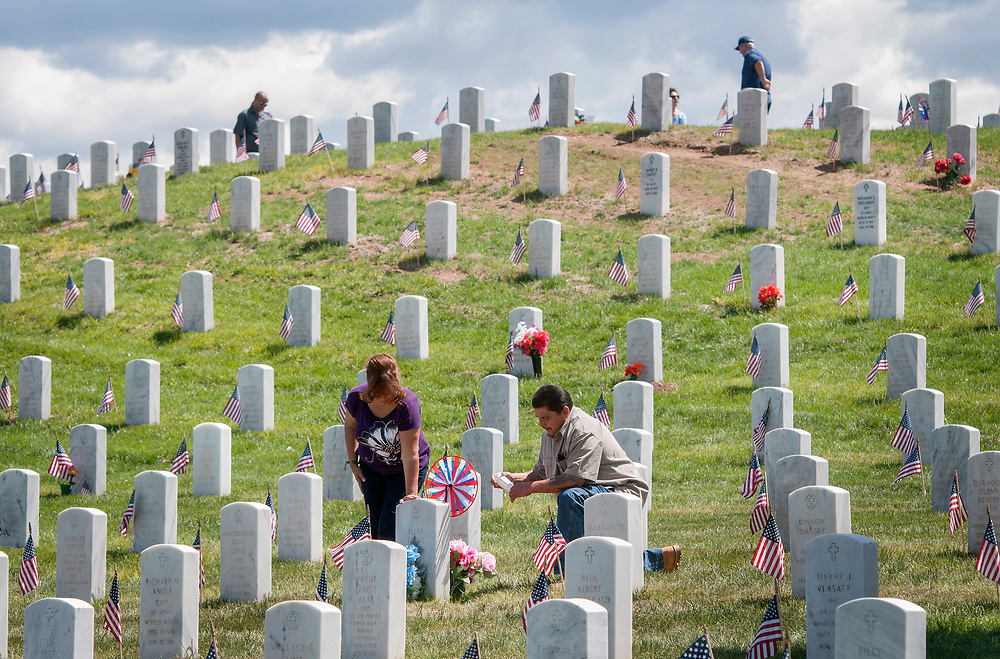 em052917b/a/Mary Salas-Sedillo and her husband Charlie Sedillo, from Albuquerque, pray next to the grave of Salas-Sedillo's mother and father, Elias and Felia Salas at the Santa Fe National Cemetery on Memorial Day, Monday May 29, 2017. Elias Salas was in WWII and was taken prisoner and forced into the Bataan Death March. (Eddie Moore/Albuquerque Journal