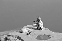 "India, Khajuraho,1999. A ""dhobi wallah,"" or laundry man, takes a moment to eat before performing a daily miracle - clean white clothes from less than clean conditions."