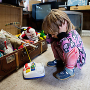 Linköping, Sweden, August 19, 2012. Stolplyckan collective, one of the biggest in Sweden with 180 apartments. A girl plays with toys inside the recycling of the collective, storage for second-hand items, where everyone can leave something and get something useful.