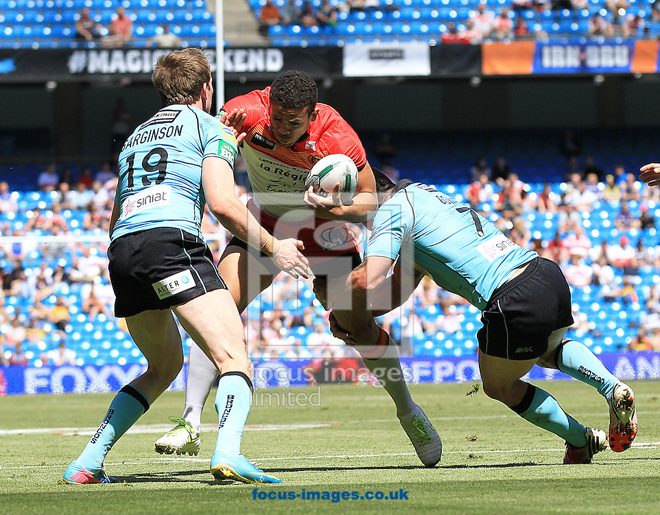 Picture by Richard Gould/Focus Images Ltd.+447814 482222 .25/05/2013 .Kevin Larroyer of Catalans Dragons is tackled by Daniel Sarginson (L) & Craig Gower of London Broncos during the Super League match at the Etihad Stadium, Manchester.