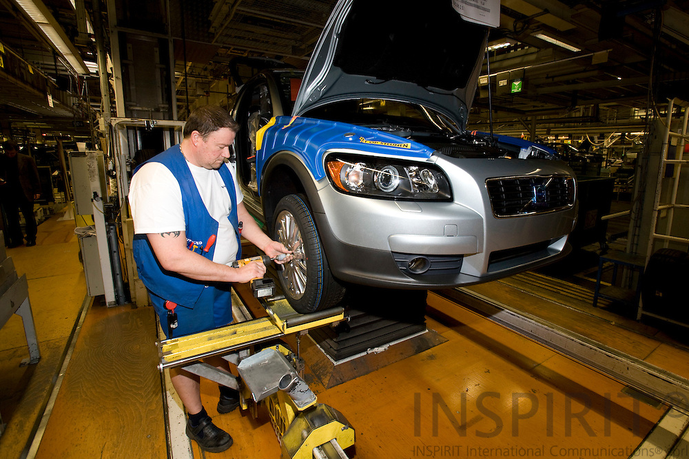 GHENT - BELGIUM - 01 APRIL 2008 --  Worker fitting wheels at the assembly line at Volvo Cars Gent. Photo: Erik Luntang
