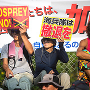 OKINAWA, JAPAN - AUGUST 19 : Anti U.S base protesters holding a placards to protest against the construction of helipads in front of the main gate of U.S. military's Northern Training Area in the village of Higashi, Okinawa Prefecture, on August 19, 2016. Japanese government resume construction of total six helipads in a fragile ten million year old Yanbaru forest that is home to endemic endangered species such as the Okinawan rail and Okinawa wood pecker. (Photo by Richard Atrero de Guzman/NURPhoto)