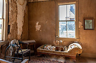 Deteriorating chaise lounge and interior of Miller House at Bodie State Historic Park. Visitors can go inside this decrepit home, which looks much like a haunted house.