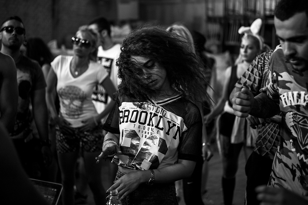 """Tehran, Iran- June, 2015: <br /> A girl dancing in an underground party on the first day of Ramadan.<br /> """"There are two societies in Iran. The one you see on the surface and the one that lives underground"""". This is a sentence that the modern non-religious new generation of iranians reapeat over and over again. They are actors, street artists, singers and party animals influenced by the western culture that is restricted by the islamic law settled on the Islamic Republic of Iran. The theocratic Constitution forbids the use of alchool, any music sang by women and any kind of art not accepted by the mullahs regime. But the underground people always find a way to do what they like: they make tatoos in basements, parties in hidden factories and music albuns on home studios.<br /> In spite of belonging to a small share of the iranian society – around 15%, they say - the liberal iranians are showing that not all the country supports the dogmas of the Supreme Leader. Their struggle is not often political but social, as they know the best way to fight against the strict system is to spread the word on the underground layer of the society, in order to changing mentalities slowly. The regime's control is hard such as the risk to be caught by the autorithies. """"So when we make a party, we party hard, because we know that it can be the last one"""", says Farid, a firedancer and party promotor.<br /> This feature follows the life of an actor, a tatoo artist, a firedancer and party promotor, a rapper, a woman singer and a street artist on the most free and hidden spots of Tehran. Hidden and free in a country of paradoxes."""
