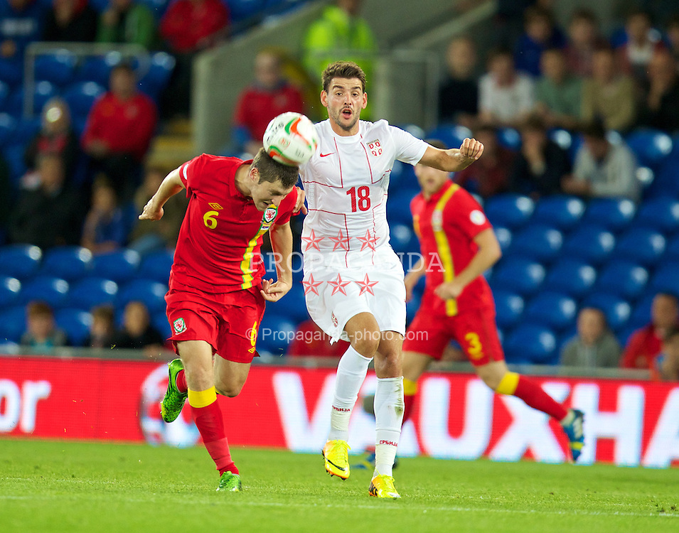 CARDIFF, WALES - Tuesday, September 10, 2013: Wales' Ben Davies in action against Serbia's Filip Djordjevic during the 2014 FIFA World Cup Brazil Qualifying Group A match at the Cardiff CIty Stadium. (Pic by David Rawcliffe/Propaganda)