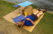 A man rests on a stretch of grass, his face shielded from a bright sky beneath a camping stool during a particularly hot afternoon at the Henley Royal Regatta boat races, England. Wearing shorts, sandals and the quintessentially English socks, the man sleeps soundly while on the river, high-society, serious rowing and general clowning around on the rural Thames make for a busy and tiring afternoon.