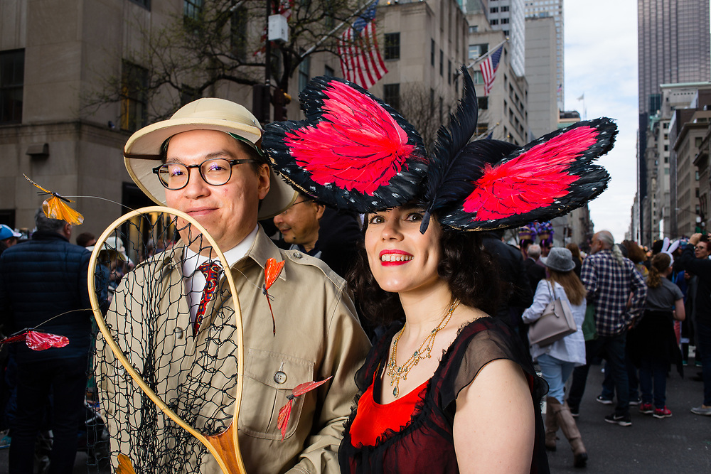 New York, NY - 21 April 2019. A lepidoptrist and his prey at the Easter Bonnet Parade and Festival on New York's Fifth Avenue.