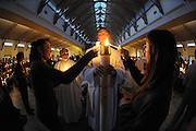 Catholics light candles from the Easter candle during Easter Vigil Mass. (Sam Lucero photo)