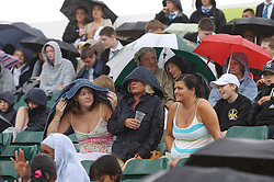 Liverpool, England - Wednesday, June 13, 2007: Fans shelter from the rain on centre court as they wait for Bjorn Borg during day two of the Liverpool International Tennis Tournament at Calderstones Park. (Pic by David Rawcliffe/Propaganda)