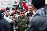 Un militaire qui a tenté d'empêcher le pillage de la Gare centrale de Tunis, place de Barcelone, est raccompagné par les manifestants qui l'embrassent et le remercient pour ne pas être intervenu plus tôt lors d'affrontements avec les forces de police. // Des affrontements entre la police et les manifestants ont éclaté dans le centre de Tunis, notamment avenue Habib Bourguiba, faisant (selon Associated Press) 3 morts (prétendument par balle) et 12 blessés parmi les manifestants, Tunis le 26 février 2011.