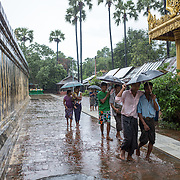 "Visitors brave a downpour at the Myazedi (or Mya Zedi) Pagoda, in the northern part of Myinkaba Village, just woth of Old Bagan. Myazedi translates as ""emerald stupa."""