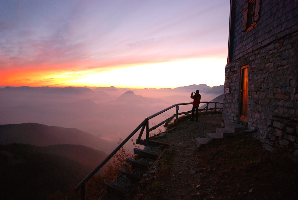 The small figure of a climber stands on the balcony behind the Purtscheller House Alpine hut, taking a photo of the sun setting above the misty Berchtesgaden Alps.