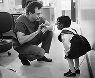 Dr. Michael Glick (left) shows a young patient a trick where he removes his thumb from his hand in 1989 at the Infectious Disease Clinic at Temple University in Philadelphia, Pennsylvania. The Infectious Disease Clinic at Temple University, was established in 1988 by Dr. Glick to treat people with HIV from throughout the region. (Photo by William Thomas Cain/Cain Images)