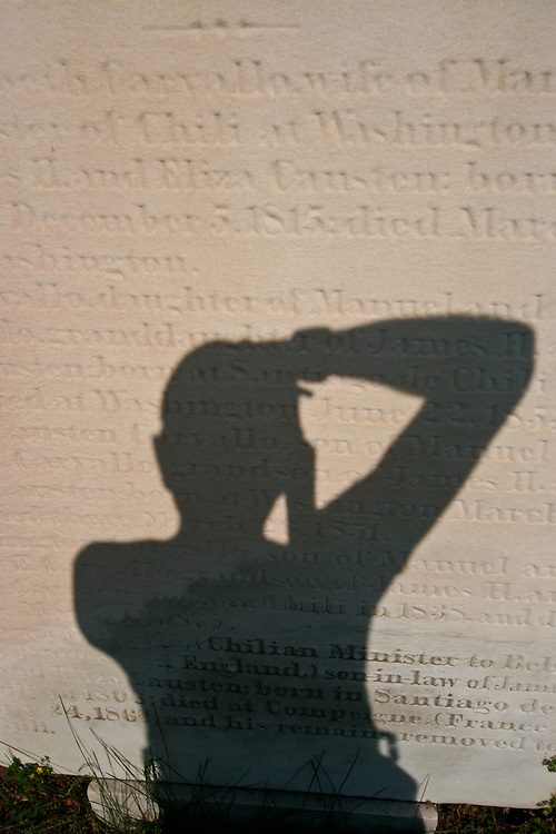The photographer's shadow falls on a gravestone.
