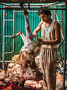 12 SEPTEMBER 2016 - BANGKOK, THAILAND: Freshly sacrificed goats and rams are skinned and cleaned during the Qurbani (ritual sacrifice of livestock) at the celebration of Eid al-Adha at Haroon Mosque in Bangkok. Eid al-Adha is also called the Feast of Sacrifice, the Greater Eid or Baqar-Eid. It is the second of two religious holidays celebrated by Muslims worldwide each year. It honors the willingness of Abraham to sacrifice his son, as an act of submission to God's command. Goats, sheep and cows are sacrificed in a ritualistic manner after services in the mosque. The meat from the sacrificed animal is supposed to be divided into three parts. The family retains one third of the share; another third is given to relatives, friends and neighbors; and the remaining third is given to the poor and needy.          PHOTO BY JACK KURTZ