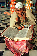 INDIA, RELIGION, CEREMONY Portrait of a Hindu priest reading scriptures before a wedding ceremony  in a village in Northern India