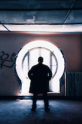 silhouette of a man in front of a window in an old abandoned building