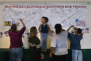 Family and friends of troops sign there names and give support for the troops. (center) Lena Brown 5 waits for pen so she can give her best wishes to the troops as her cousin Heather Sugar 14 makes sure she doesn't fall.  More than 100 Sacramento-based members of the Guard's 2668th Transportation Company had a family get-together before they left for Iraq. PIcture taken at the National Guard Center on Meadowview Road, Tuesday, October 5, 2004.