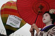 """'Kosen"""", a 20 year old Maiko girl from Kyoto, stands in front of a hot air balloon bearing a sign marking the implementation of the Kyoto Protocol Agreement. The Agreement comes into force on Febuary 16th 2005, and was marked by events and conferences in Kyoto involving Greenpeace and Solar Generation, a youth group environmental NGO."""
