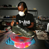 Surrounded by shoes brought in by customers, Edwards works on customizing a pair of Jordan 9's in the back of her store. She brushes on an acrylic leather paint to bring the shoe from its original black color to an olive green.