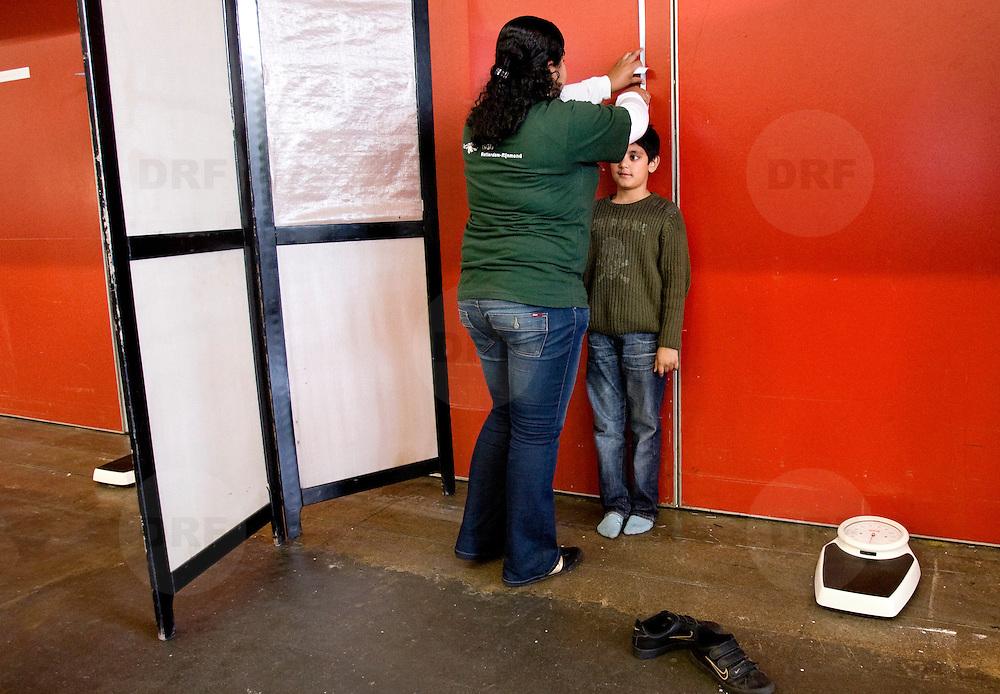 """Nederland Rotterdam 8 oktober 2008 Foto: David Rozing ..Lengte kinderen wordt gemeten tijdens Vaccinatiedag in Ahoy.. Vaccinatiedag AHOY in teken van overgewicht en opvoeden.Vandaag werden in AHOY Rotterdam zo'n 4.000 kinderen uit het Noorden van Rotterdam gevaccineerd tegen de infectieziekten difterie, tetanus en polio (DTP) en bof, mazelen en rode Hond (BMR). Na de vaccinaties kunnen ouders gebruik maken van advies van een diëtist en van een pedagoog..Twee keer per jaar houdt de GGD Rotterdam-Rijnmond een grote vaccinatiedag voor 9-jarigen. Op 8 oktober krijgen ongeveer 4000 kinderen een vaccinatie tegen ernstige infectieziekten als difterie, tetanus en polio (DTP) en/of bof, mazelen en rode Hond (BMR). Enkele 9-jarigen krijgen ook nog een Hibvaccinatie (tegen Haemophilus influenzae type b). Er worden ook zo'n 500 kinderen gevaccineerd die zich pas in Rotterdam hebben gevestigd. Voor deze kinderen moet soms het buitenlandse schema worden ingepast in het Nederlandse Rijksvaccinatieprogramma (RVP).""""??Meten, wegen en opvoedingsadvies??De GGD grijpt de vaccinatiedag aan om méér te doen dan de bescherming tegen infectieziekten. De kinderen kunnen na de twee prikken meteen doorlopen voor het bepalen van hun lengte en gewicht. Er zijn diëtisten aanwezig, zodat ouders en kinderen zich kunnen laten adviseren over gezonde voeding en beweging. En als ouders vragen hebben over de opvoeding van hun kind kunnen zij deze ter plekke stellen aan één van de veertien aanwezige pedagogen. ??Activiteiten voor kinderen over ontbijten??Er zijn allerlei activiteiten te doen in het teken van ontbijten. Een diëtist maakt samen met kinderen gezonde ontbijtjes. Er is een muzikale theatervoorstelling over het belang van ontbijten. Op een groot scherm wordt een filmpje vertoond en met een ontbijtquiz zijn drie fietsen te winnen. Alle kinderen krijgen een attentie mee naar huis.??Actieprogramma Voeding en beweging??De GGD houdt deze voedings- en bewegingsactiviteiten in het kader van het actiep"""