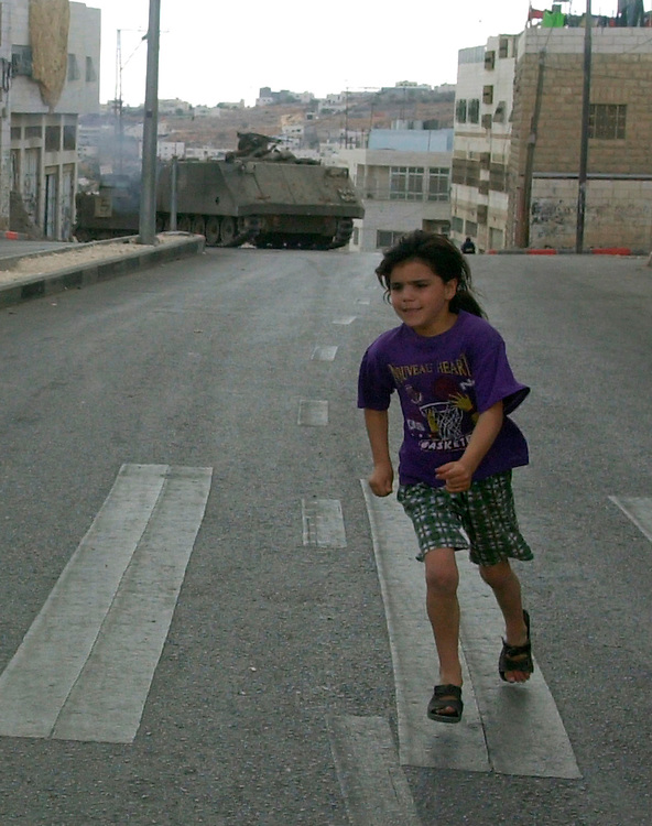A Palestinian girl runs from an armored personell vehicle with a mounted automatic weapon moving towards her,as a tank sits behind the armored vehicle overlooking the West bank town of Hebron Friday Oct. 5, 2001. The Israeli army entered Palestinian controlled areas in Hebron occupying Palestinian homes and leaving at least five Palestinians dead.