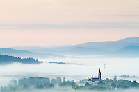 September sunrise in the Bieszczady National Park region with fog rising from the meadows around the city of Lutowiska, Poland.