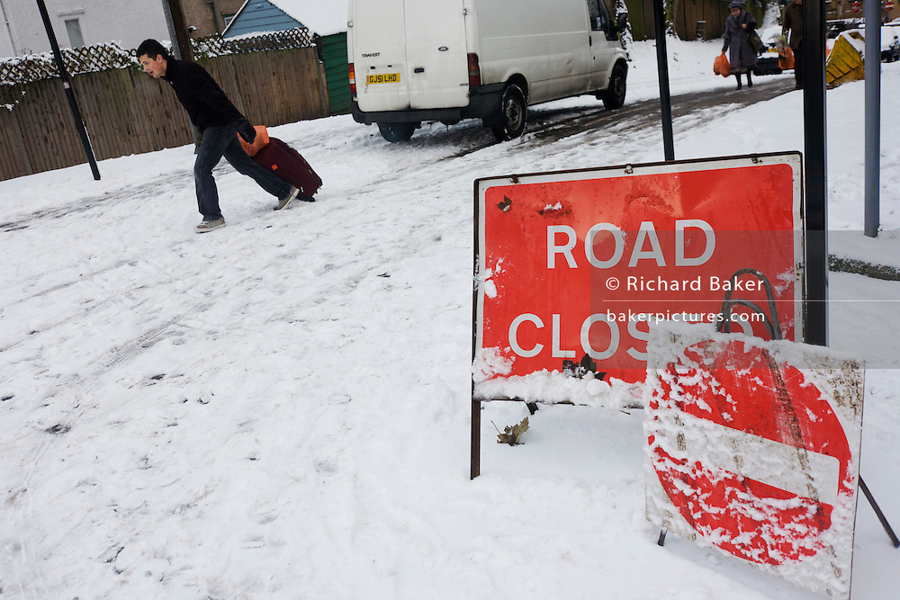 A Closed Road sign and a local male shopper passes-by on a hill in south London during wintry snows.