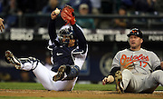 Seattle Mariners' catcher Kenji Johjima, left, holds up the ball after Aubrey Huff was tagged out at home in the fifth inning of baseball action in Seattle on Wednesday, April 23, 2008. (AP Photo/Kevin P. Casey)