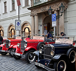 Prague, Czech Republic:  Paint shining and chrome gleaming, a series of antique cars await tourists in a small square along Karlova street, just off Old Town Square. Touring in vintage cars is a popular way to explore this city.