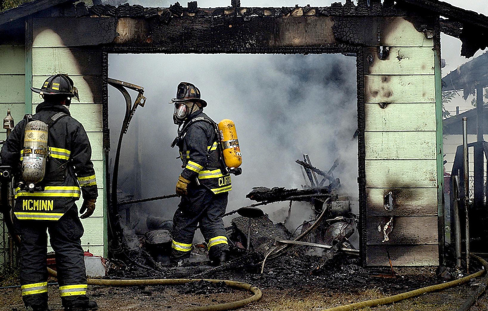 JEROME A. POLLOS/Press..Northern Lakes firefighters Bill Clifford, from right, and Richard McMinn look for hotspots on a garage that caught fire on Wednesday in Hayden on Hilgren Avenue. The fire was started by an air compressor that malfunctioned in the garage and the fire quickly spread to the back portion of the residence.