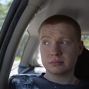 ROCKVILLE, MD - JUL25: John Bucknam, 18, who has autism, rides in the back of the car with his mom after camp, to their home in Rockville, MD, July 25, 2014. The Bucknam's have a series of locks on their doors to keep John from wandering off. (Photo by Evelyn Hockstein/For The Washington Post)