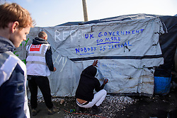 © Licensed to London News Pictures. 23/10/2016. Calais, France. A group of British charity workers write anti-British government slogans on the wall of a temporary building in the 'Jungle' camp in Calais ahead of an it's demolition, which is scheduled for this week. French authorities have given an eviction order to thousands of refugees and migrants living at the makeshift living area of the French coast. Photo credit: Ben Cawthra/LNP