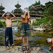 Children bath in the river running through a Chinese village. <br /> <br /> Shielded from the rest of Chinese civilization by a cascade of steep mountains, this village and the other surrounding lush villages have kept their Dong minority traditions and arts from centuries ago.<br /><br />With a history that goes back to the Tang dynasty, the area is adorned with stunning wooden Flower Bridges, bell towers and cascades of beautiful old houses. The Dong people have no written language, but use fine embroidery to communicate their love.<br /><br />Yet, as highways and tunnels plough through these mountains, the future of the village&rsquo;s 525 households is at crossroads. There is already a government blueprint to turn Dimen into a satellite town in the coming three years, as China embarks on its latest urbanization drive.