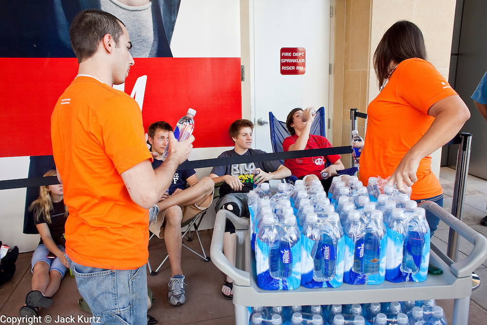 12 JUNE 2009 - SCOTTSDALE, AZ: Apple employees hand out water to people waiting to get into the store during its grand opening in Scottsdale, AZ. The outlet will be Arizona's largest Apple Store, occupying nearly 10,000 square feet in the Outdoor Lifestyle Center in the Scottsdale Quarter. The store, the fifth in the Phoenix area, uses a radically different design from other Apple Stores in some respects, ceilings in the building are approximately 20 feet high, and lined with a 75-foot long skylight, reducing dependence on artificial lighting. Aiding the skylight is an all-glass front and rear, permitting visitors to see directly through the store. PHOTO BY JACK KURTZ