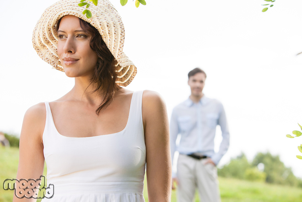 Thoughtful young woman looking away with man in background at park