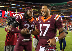 Sep 3, 2017; Landover, MD, USA; Virginia Tech Hokies safety Terrell Edmunds (22) and Virginia Tech Hokies quarterback Josh Jackson (17) celebrate after beating the West Virginia Mountaineers at FedEx Field. Mandatory Credit: Ben Queen-USA TODAY Sports
