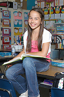 School girl with book in classroom, portrait