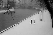 France. Paris.  the Seine river , pedestrians on Quai des grands Augustins under the snow