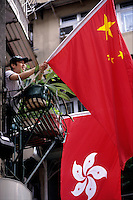HONG KONG- JULY 1: A man puts out a Chinese flag on his balcony next to the new Hong Kong flag in Central on July 1, 1997 in Hong Kong, China. On July 1, 1997 Hong Kong was handed over to China from the United Kingdom after being a colony for 150 years. (Photo by David Paul Morris) ..