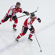 Dax Lauwers #44 of the Northeastern Huskies (R) and Adam Reid #8 of the Northeastern Huskies in action during the Frozen Fenway game between The Northeastern Huskies and The UMass Lowell Riverhawks at Fenway Park on January 11, 2014 in Boston, Massachusetts.