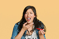 Portrait of a young woman eating red hot chili pepper over colored background