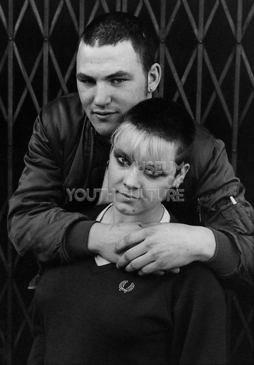 Skinhead couple, man with his arms round womans shoulder