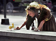 Ruthie the Duck Lady, a.k.a., the Duck Girl, gives a baby duck a bath in the fountain next to Cafe du Monde in the French Quarter of New Orleans, Louisiana; Ruthie was the French Quarter's most notable and beloved eccentric character