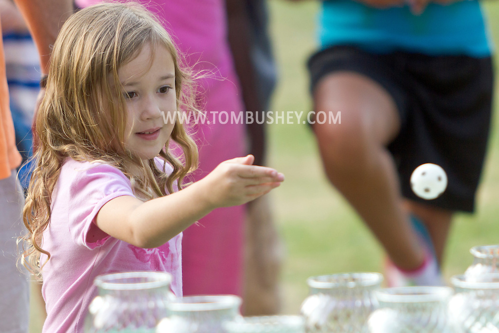 Middletown, New York - A girl tosses a ball at jars in an attempt to win a goldfish during the Camp Funshine Carnival Night on Aug. 16, 2012. The night celebrated the Middletown YMCA summer camp, which ended the next day.