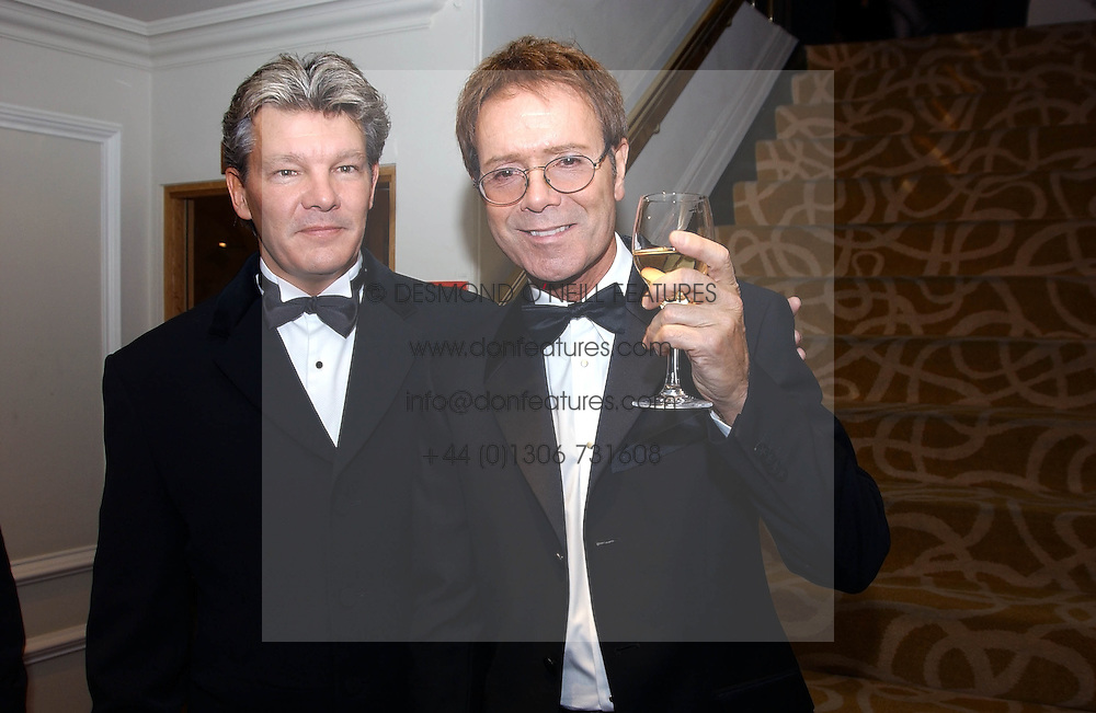 Left to right, RUSS LINDSAY husband of Caron Keating and SIR CLIFF RICHARD at The Caron Keating Foundation Dinner in honour of the late TV presenter who died in April 2004, held at The Savoy, London on 4th October 2004.<br />