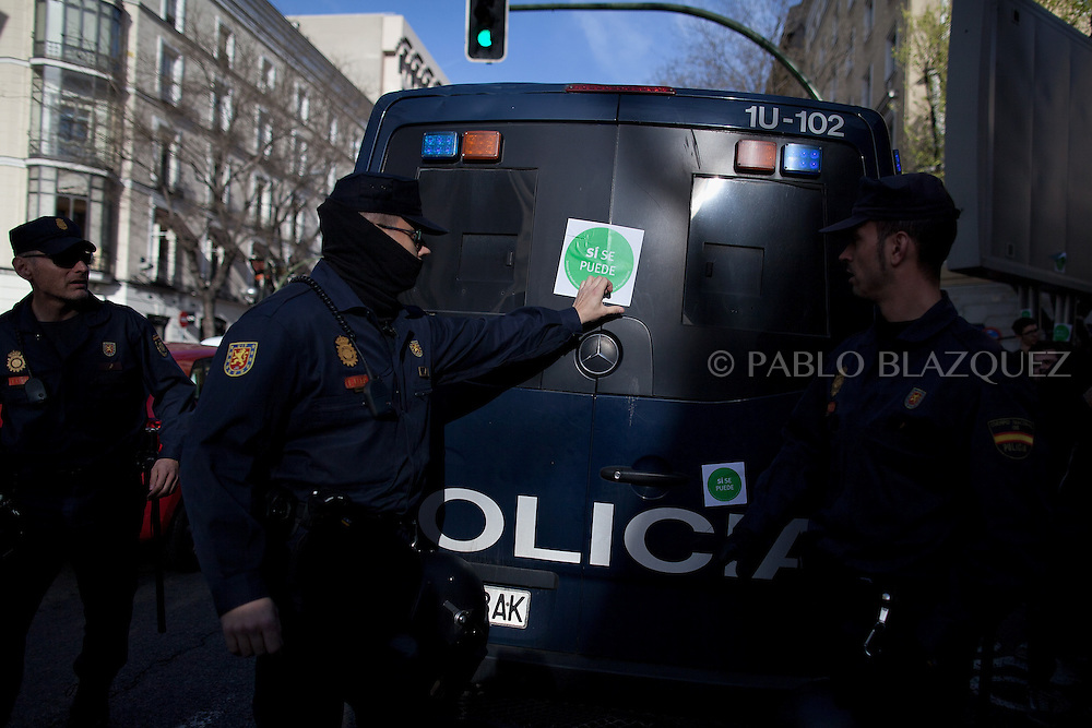 Riot police removes a sticker reading 'yes we can' from a police van during an 'escrache' near the house of Spain's President of Parliament Jesus Posadas on April12, 2013 in Madrid, Spain. The Mortgage Holders Platform (PAH) and other anti evictions organizations have been organizing 'escraches' for several weeks under the slogan 'There are lives at risk' to claim the vote for a Popular Legislative Initiative (ILP) to stop evictions and facilitate social rent, outside Popular Party deputies' houses and offices. 'Escraches' are a form of peaceful protest that were used in Argentine in 1995 to publically denounce pardoned members of the dictatorship for their crimes at their doorsteps.