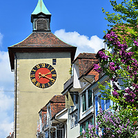 Biel Gate Clock Tower in Solothurn, Switzerland <br /> The old, historic part of Solothurn, Switzerland, sits on the left bank of the Aare River. A 17th century wall surrounds the colorful baroque and Renaissance buildings.  This clock tower is part of the 13th century Biel Gate.  It is the western entrance to the Old Town's cobblestone streets.  It is also called Bieltor which means the gate towards the town of Biel.