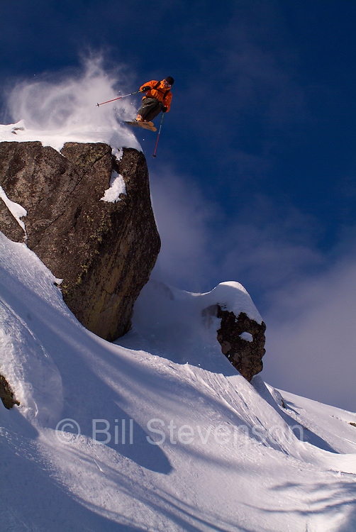A photo of a man jumping off a cliff on skis on Donner Summit, California.
