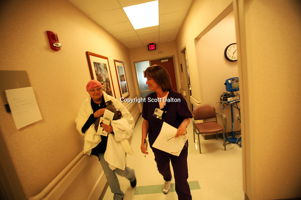 Cindy Davis, a nurse in the breast cancer division of the MD Anderson Cancer Center, in Houston walks Starla Trayal, a breast cancer patient, back to one of the examination rooms on October 8, 2009. Cindy Davis, besides being a nurse working with breast cancer patients, is herself a patient; she has stage 4 cancer and continues to work while she tries to battle her cancer. (Photo/Scott Dalton)